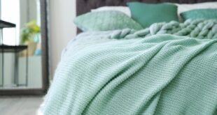 Türkisfarbene Kuscheldecke auf einem Bett