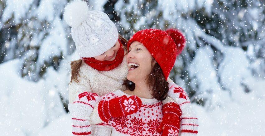 Mutter und Kind mit Wintersachen im Schnee
